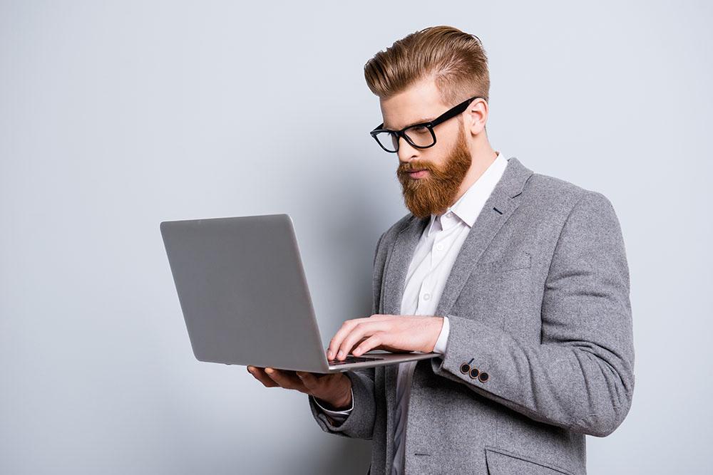 businessman in grey suit on laptop