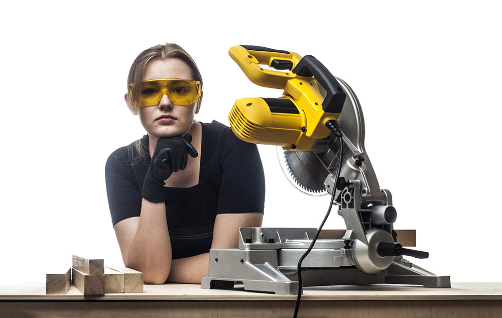 trades woman with industrial saw