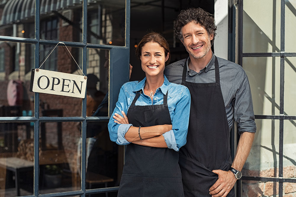 couple standing in front of new store with open sign smiling