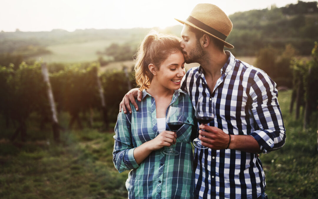 couple in vineyard with wine glasses