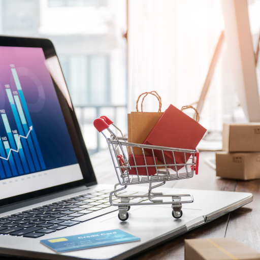 Shopping bags incart and credit card on laptop with paper boxes on table and sales data economic growth graph on screen, buying and selling services online on network, e-commerce concept